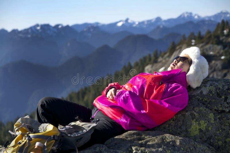 w średnim wieku kobieta Relaksuje w Ciepłym zimy świetle słonecznym przy 1st szczytem na górze Seymour Kanada, BC Ubierający w Co zdjęcia stock