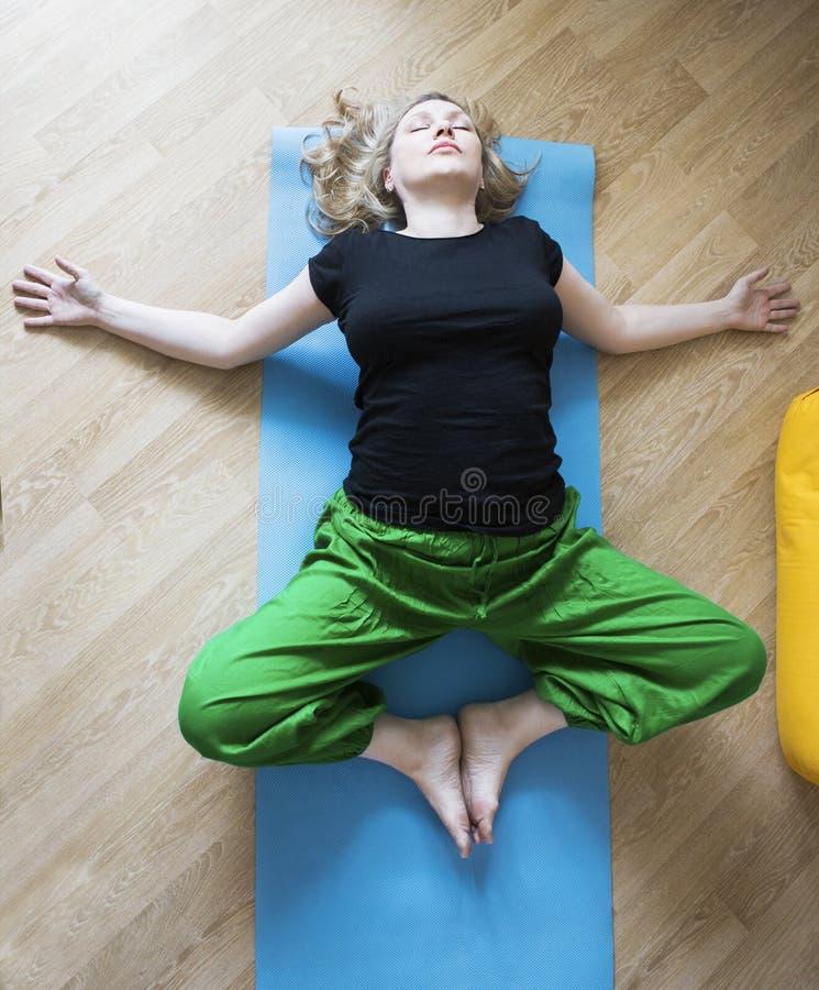 W średnim wieku kobieta robi joga indoors obrazy royalty free