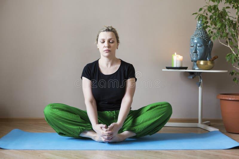 W średnim wieku kobieta robi joga indoors zdjęcia stock