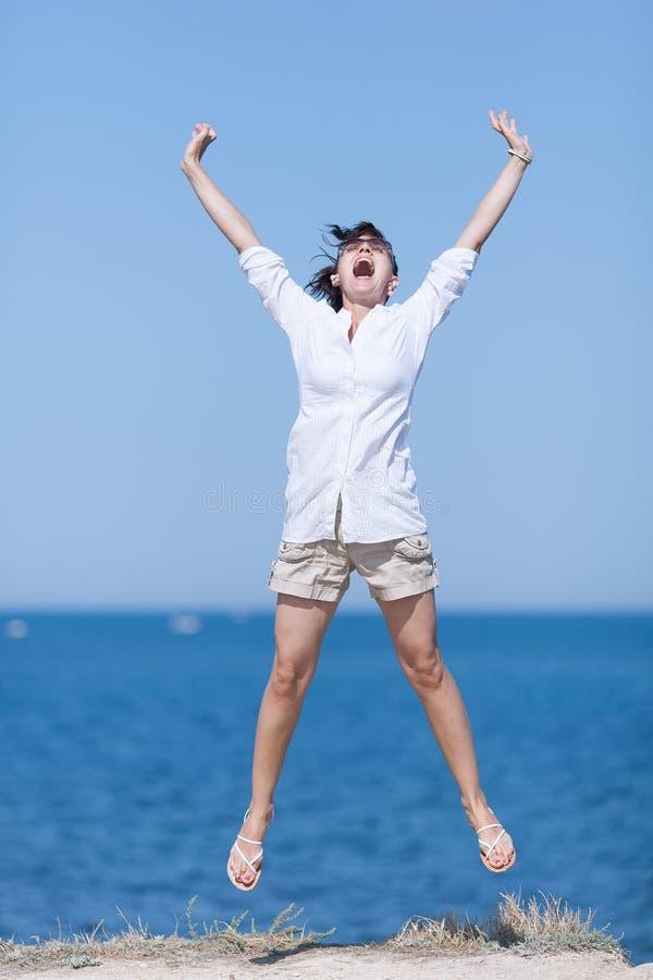 W średnim wieku kobieta skacze i krzyczy zdjęcia stock