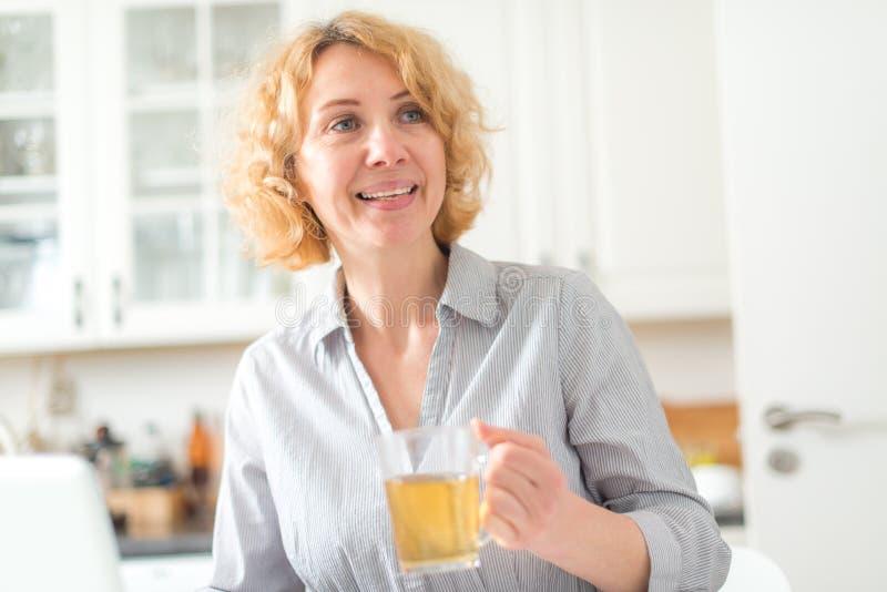 W średnim wieku kobieta trzyma filiżankę herbata zdjęcie stock