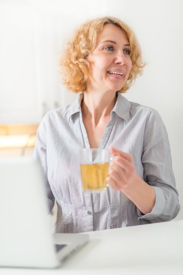 W średnim wieku kobieta trzyma filiżankę herbata obraz stock