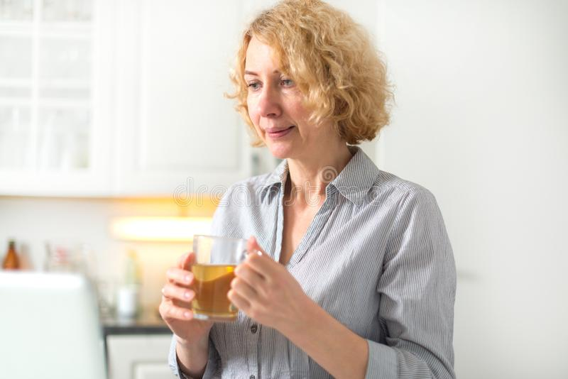 W średnim wieku kobieta trzyma filiżankę herbata obraz royalty free