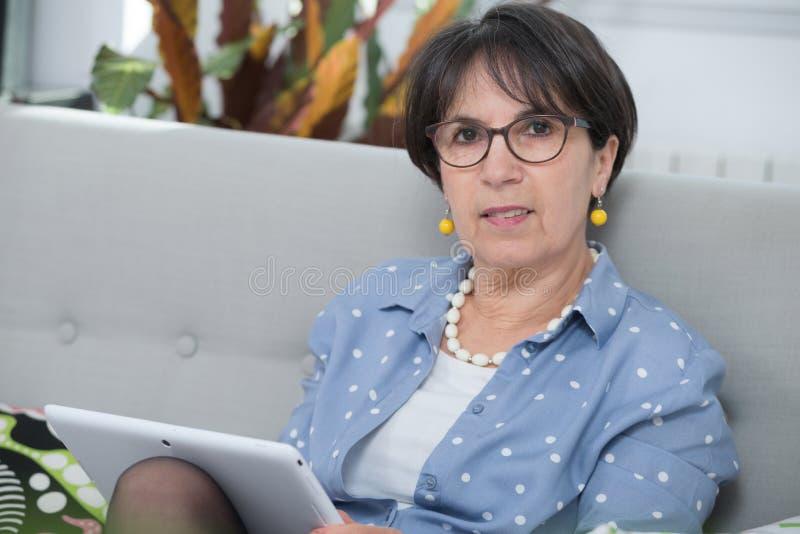 W średnim wieku kobieta używa cyfrową pastylkę w domu obrazy stock