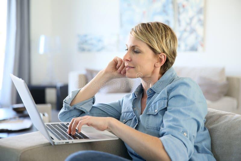 W średnim wieku kobieta używa laptop zdjęcie royalty free