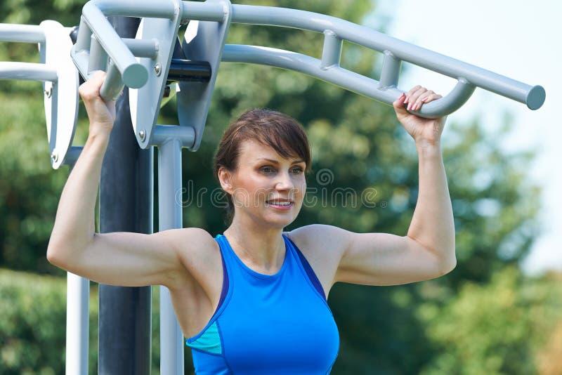 W Średnim Wieku kobieta Używa Plenerowego Gym wyposażenie obrazy stock