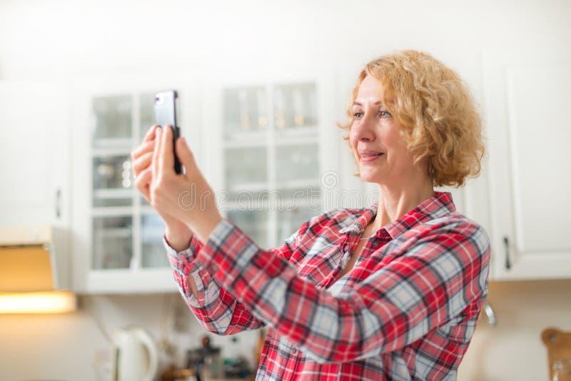 W średnim wieku kobieta używa smartphone zdjęcie stock