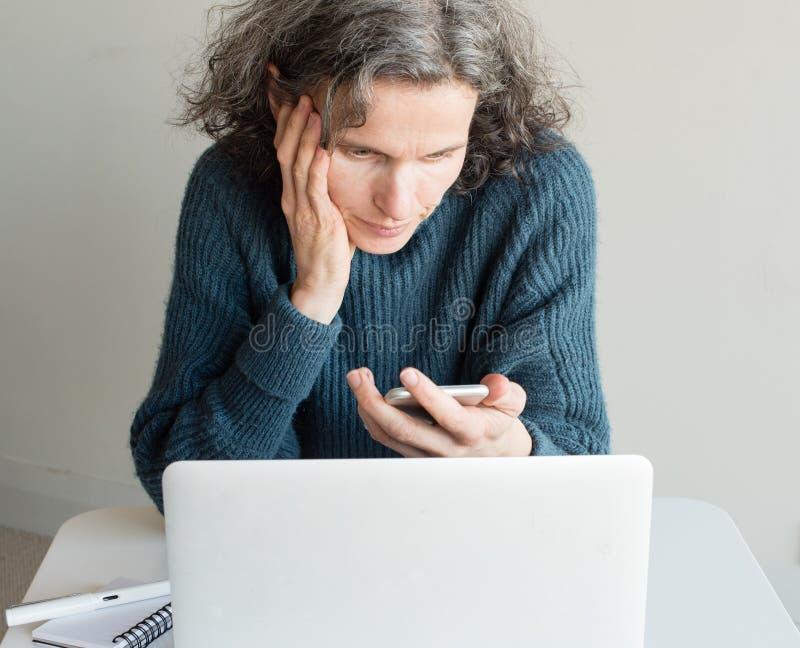 W średnim wieku kobieta udaremniająca z smartphone i komputerem fotografia stock