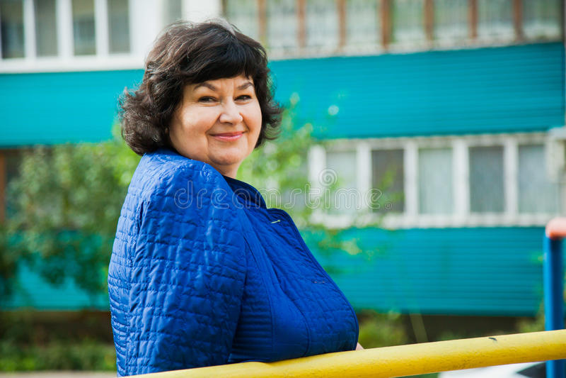 W średnim wieku kobieta wśród miasto budynków mieszkaniowych fotografia stock