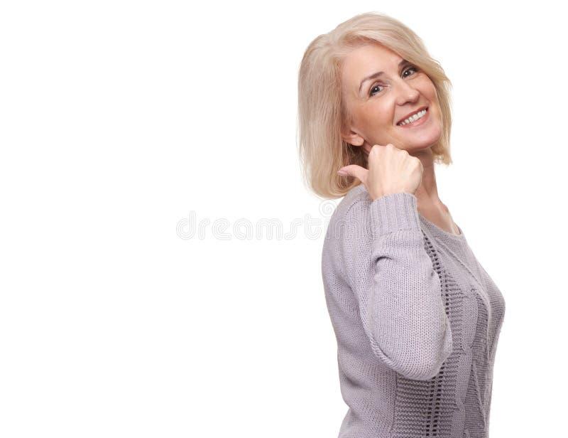 W średnim wieku kobieta wskazuje przy białym tłem fotografia royalty free