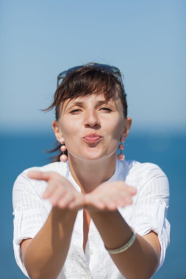 W średnim wieku kobieta wysyła lotniczego buziaka oba rękami obrazy stock