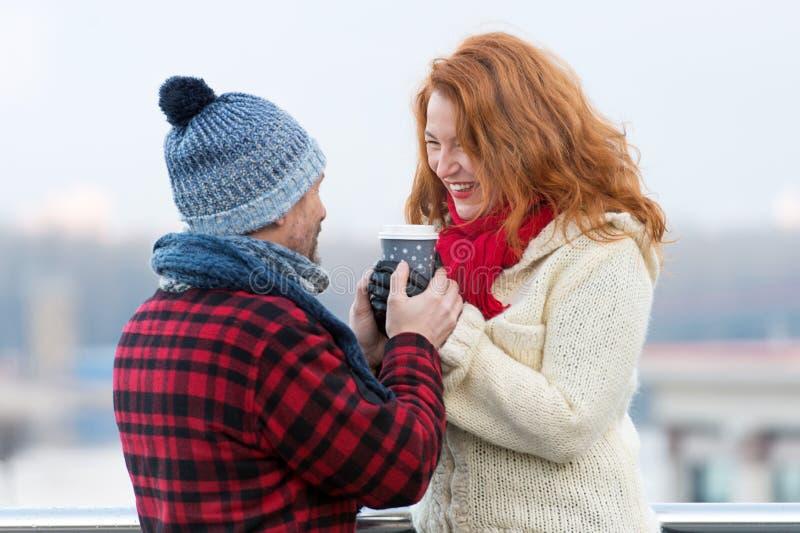 W średnim wieku kobieta z chłopaka chwyta gorącą filiżanką kawy Szczęśliwa kobieta bierze filiżankę od jej mężczyzna Par ciepłe r fotografia royalty free