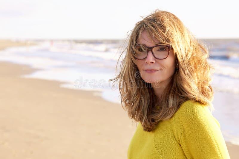 W średnim wieku kobieta z frizzy włosianym odprowadzeniem na plaży zdjęcie stock
