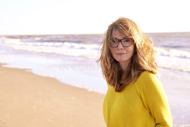 W średnim wieku kobieta z frizzy włosianym odprowadzeniem na plaży zdjęcia royalty free