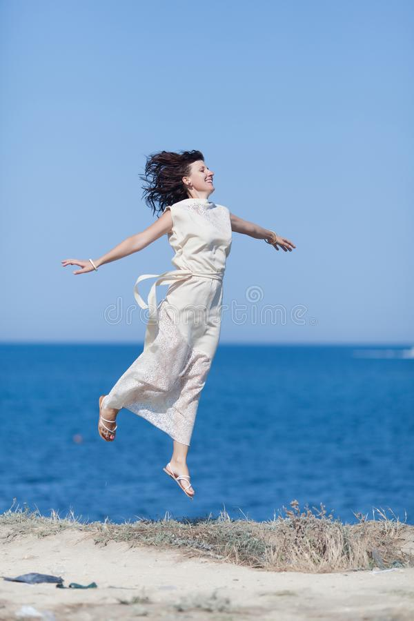 W średnim wieku kobiety chmielenie przeciw morzu z rękami szeroko rozpościerać fotografia royalty free
