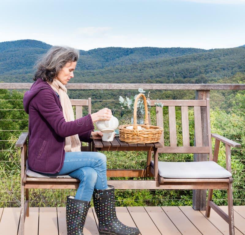 W średnim wieku kobiety dolewania herbata z krajobrazowym tłem obraz stock