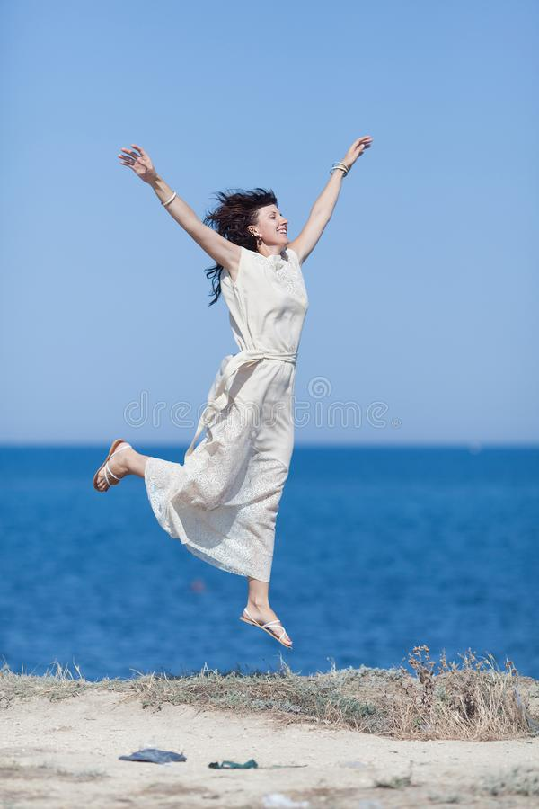W średnim wieku kobiety doskakiwanie przeciw morzu z rękami podnosić zdjęcia royalty free