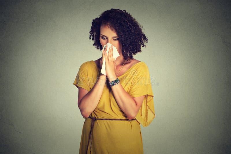 W średnim wieku kobiety kichnięcie w tkankowym dmuchaniu jej cieknący nos fotografia stock