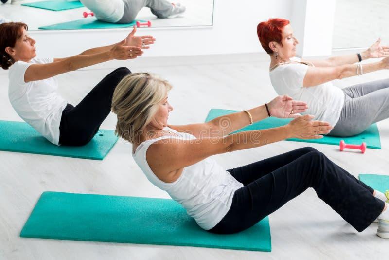 W średnim wieku kobiety robi brzusznemu ćwiczeniu w gym obrazy stock