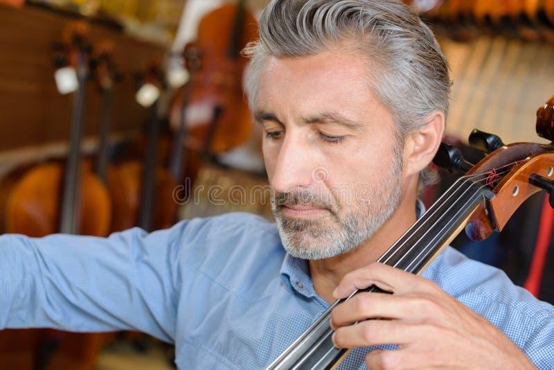 W średnim wieku mężczyzna bawić się nawleczonego instrument zdjęcia royalty free