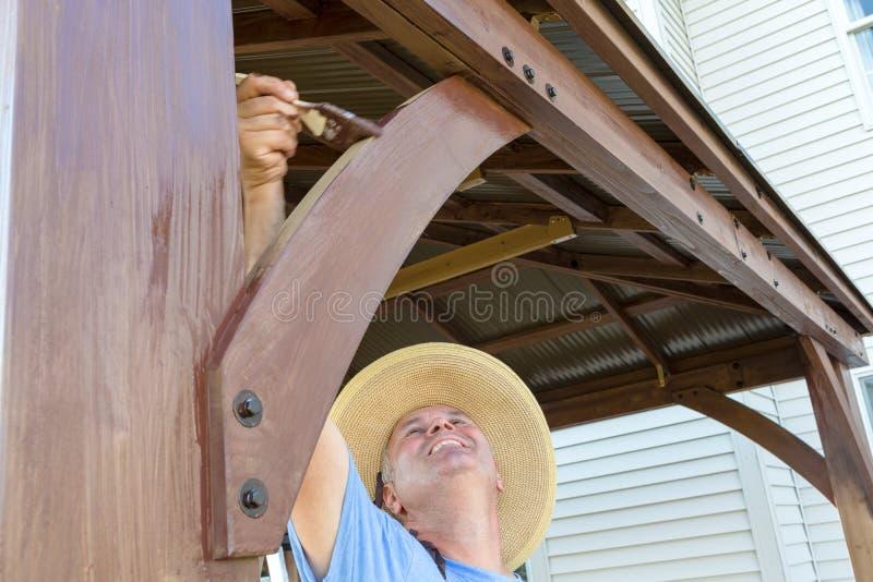 W średnim wieku mężczyzna brudzenia woodwork na gazebo obraz stock