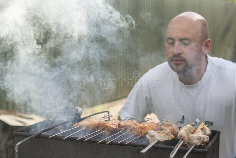 w średnim wieku mężczyzna cieszy się kulinarnego mięso na grillu czas wolny, jedzenie, ludzie i wakacje pojęcie, - szczęśliwego m obrazy royalty free