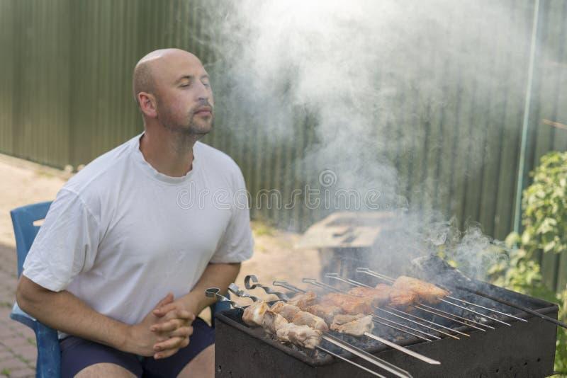w średnim wieku mężczyzna cieszy się kulinarnego mięso na grillu czas wolny, jedzenie, ludzie i wakacje pojęcie, - szczęśliwego m obraz royalty free