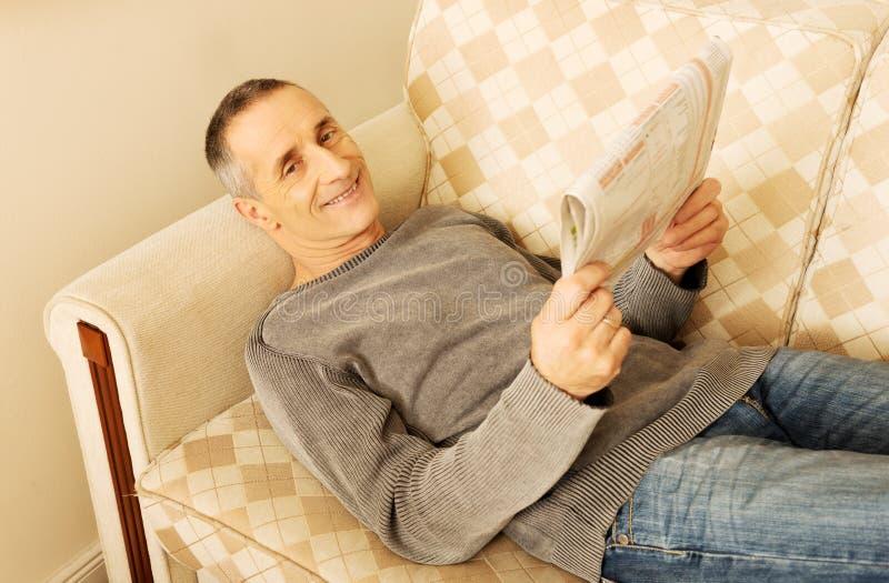 W średnim wieku mężczyzna czytelnicza gazeta w domu obrazy stock