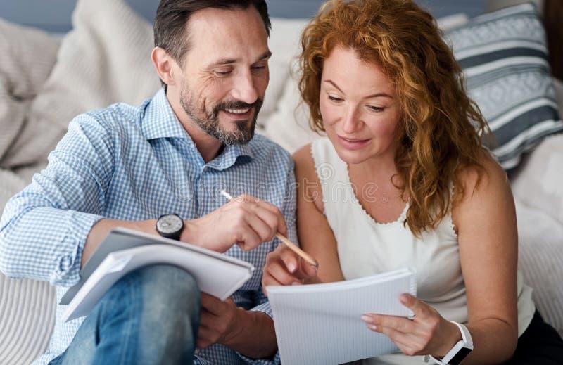 W średnim wieku mężczyzna i kobiety para robi notatkom zdjęcie royalty free