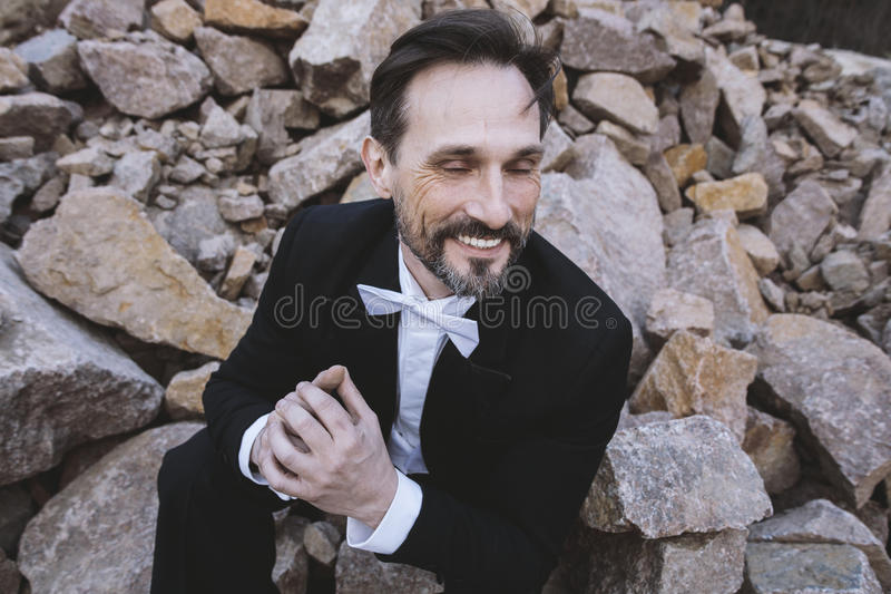 W średnim wieku mężczyzna obsiadanie na kamieniach i ono uśmiecha się z zamkniętymi oczami Dzień, plenerowy zdjęcie royalty free