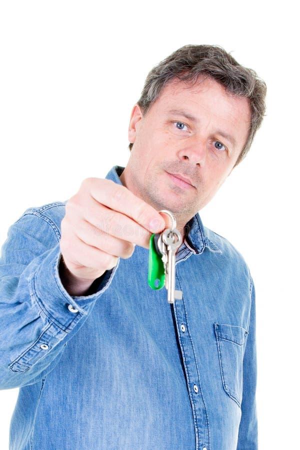 W średnim wieku mężczyzna oddaje klucze z pustym białym tłem zdjęcia stock