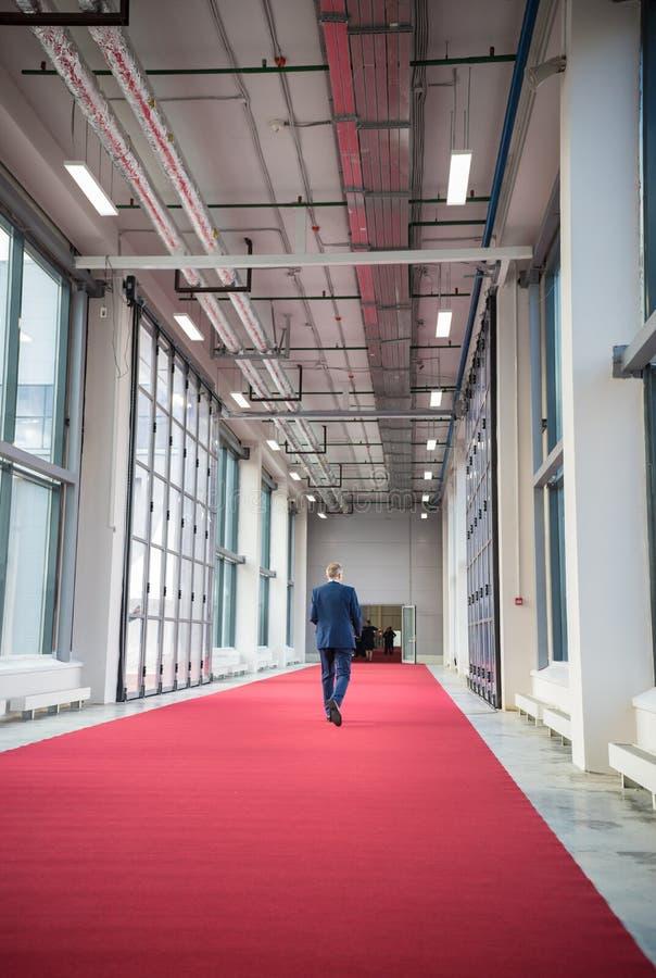 W średnim wieku mężczyzna odprowadzenie na czerwonym chodniku w kierunku sala konferencyjnej obraz royalty free