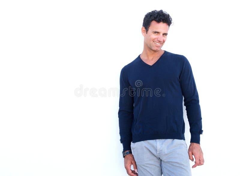 W średnim wieku mężczyzna ono uśmiecha się przeciw białemu tłu zdjęcie stock