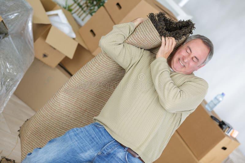 W średnim wieku mężczyzna ono zmaga się nieść wyplatającego dywanika zdjęcia stock