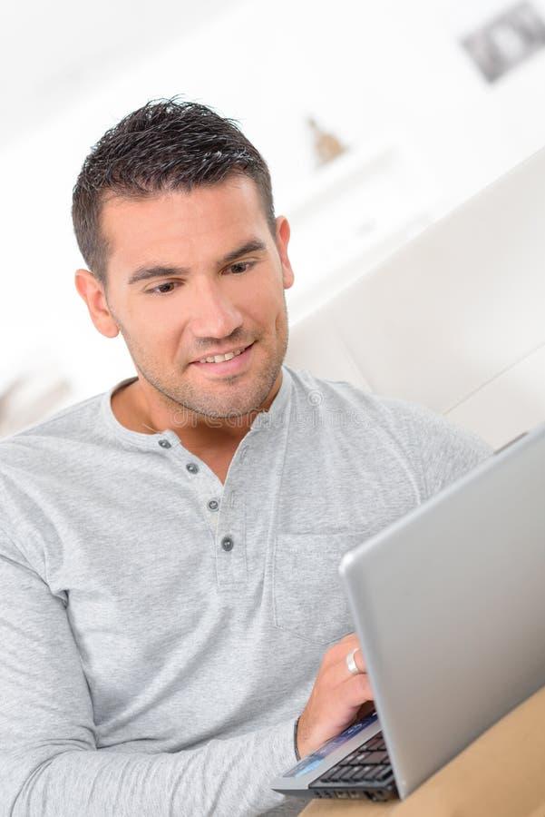 W średnim wieku mężczyzna pracuje od domu na laptopie obrazy royalty free