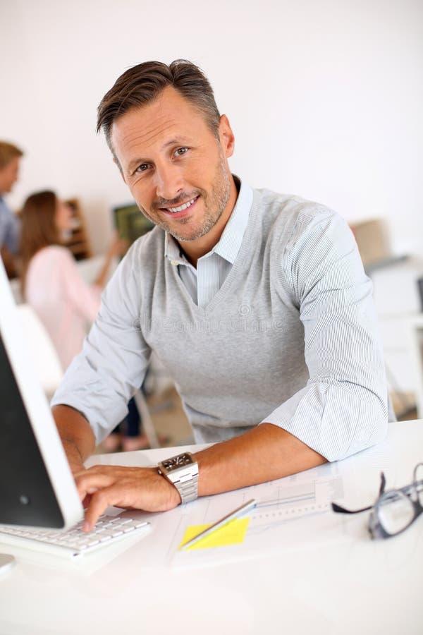 W średnim wieku mężczyzna pracuje z biznesową kobietą obraz stock