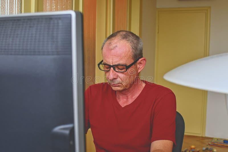W średnim wieku mężczyzna siedzi przy biurkiem z szkłami Dorośleć mężczyzna używa osobistego komputer Starszy pojęcie Mężczyzna p zdjęcie royalty free