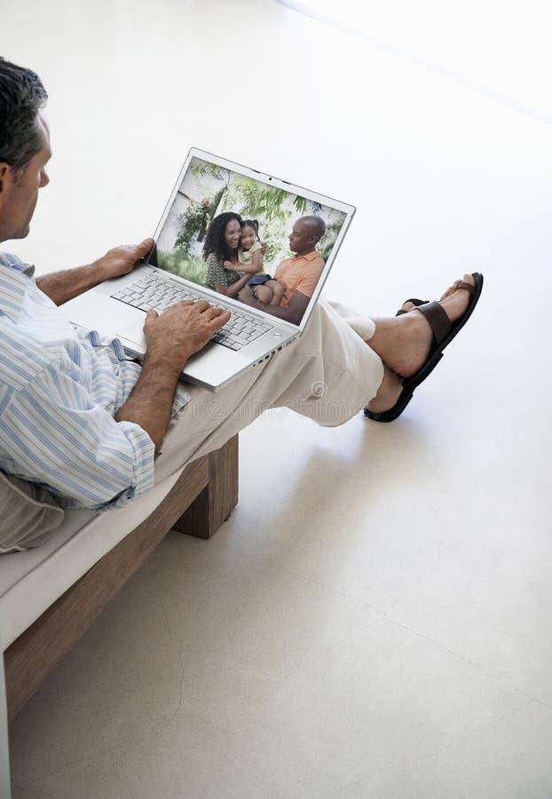 W średnim wieku mężczyzna wyszukuje przez rodzin fotografii na laptopie w domu fotografia royalty free