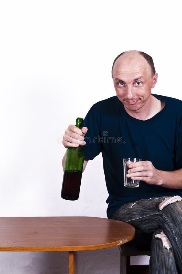 W średnim wieku mężczyzna z butelką i szkłem fotografia royalty free