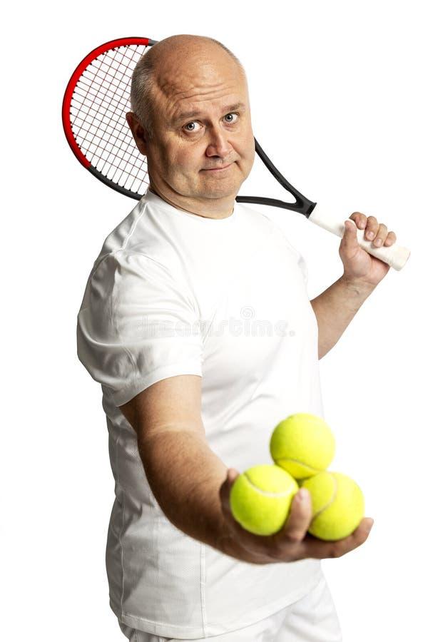 W średnim wieku mężczyzna z kantem i tenisowymi piłkami pojedynczy bia?e t?o obraz stock