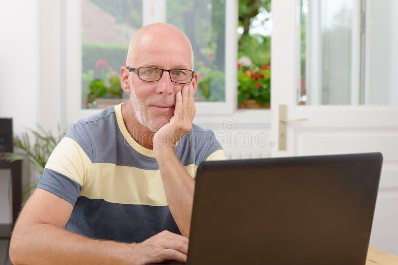 W średnim wieku mężczyzna z laptopem zdjęcia stock