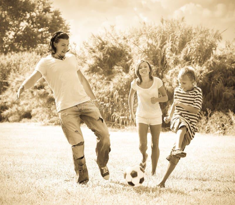 W średnim wieku para i nastolatek bawić się z piłki nożnej piłką obrazy royalty free