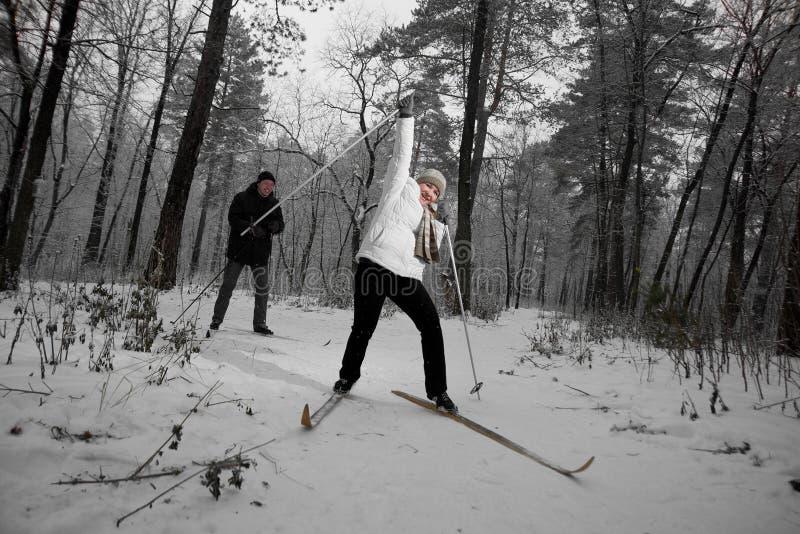W średnim wieku para na narcie w lesie zdjęcia royalty free