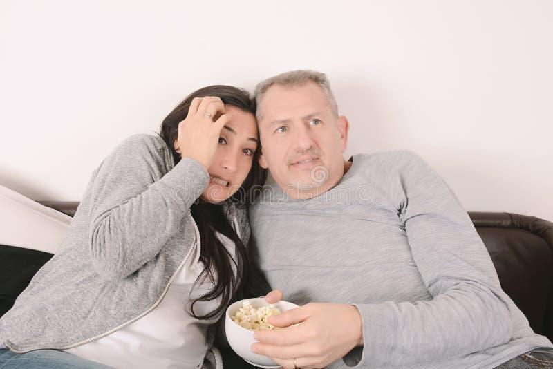 W średnim wieku para ogląda strasznego film zdjęcia stock