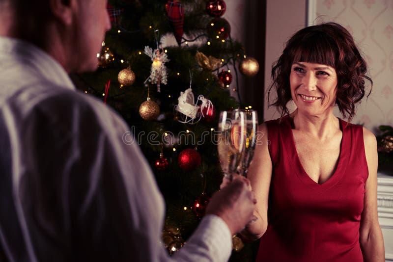 W średnim wieku para ono uśmiecha się czule podczas gdy wznoszący toast z champagn obraz royalty free