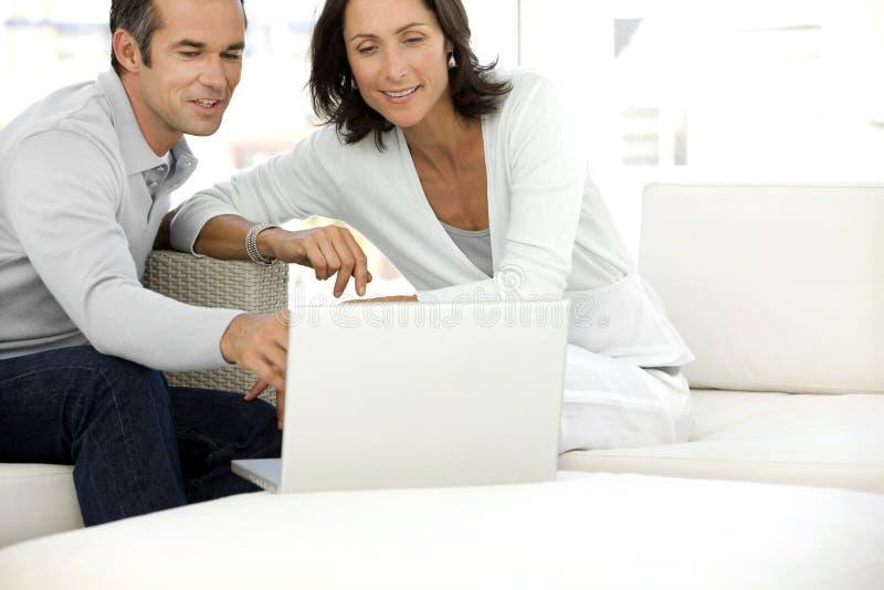 W średnim wieku para używa laptop zdjęcia stock