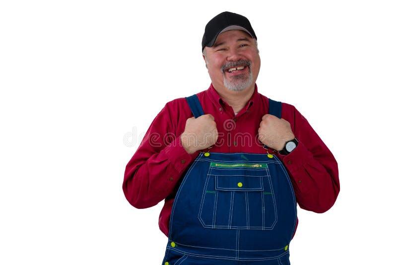 W średnim wieku pracownik w dungarees z dumnym uśmiechem fotografia royalty free