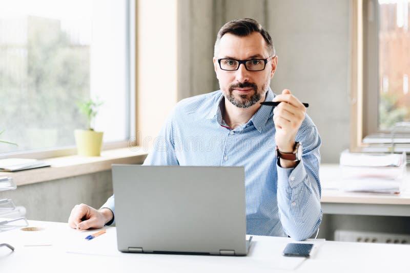 W średnim wieku przystojny mężczyzna pracuje na laptopie fotografia royalty free