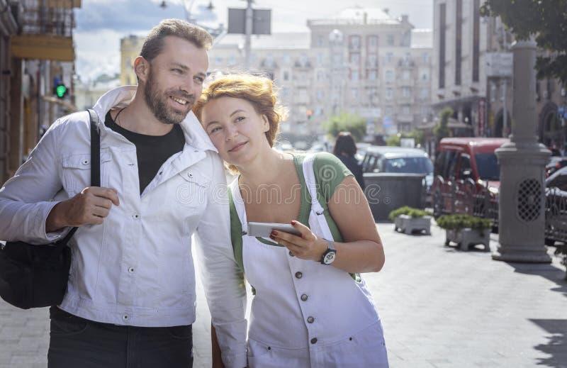 W średnim wieku rodzinny podróżować w nowym mieście z smartphone Dzień, plenerowy obraz royalty free