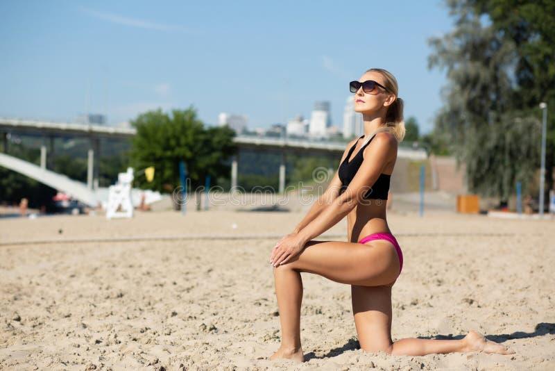 W średnim wieku sprawności fizycznej kobieta w swimsuit trenuje na plaży Przestrzeń dla teksta zdjęcia royalty free